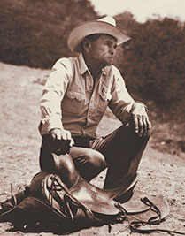 photo of Arnold R. Rojas with hand on saddle horn