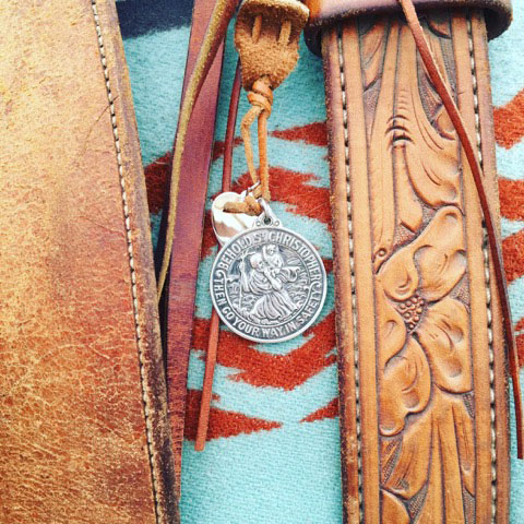 St. Christopher hanging from a saddle over a light blue and red saddle blanket